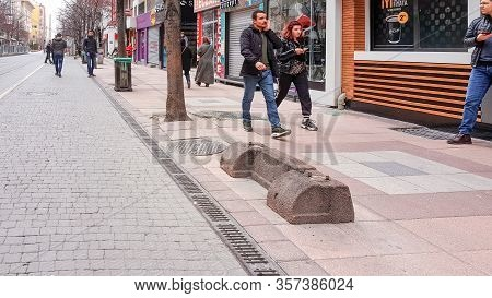 Eskisehir, Turkey - March 23, 2020: People Walking In Street During Corona Days. Bench Detached By T