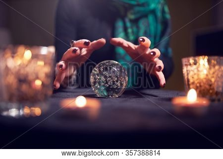 Close-up of fortune-teller's hands with ball of predictions