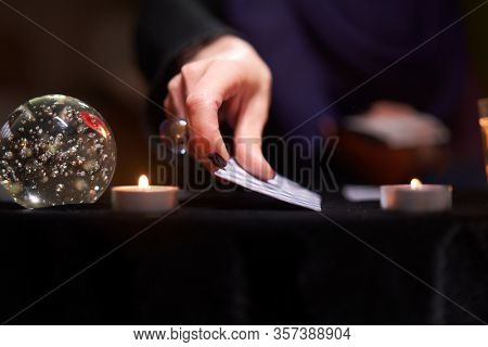 Fortuneteller female divines on cards sitting at table with candles