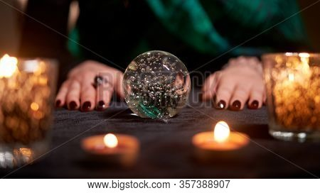Fortuneteller divining on magic ball at table with burning candles