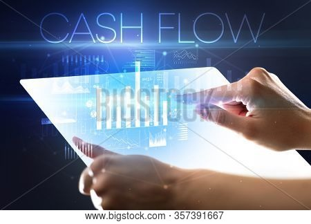 Hand holding futuristic tablet with CASH FLOW inscription above, modern business concept