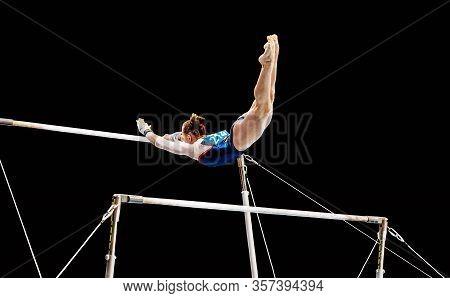 Women Gymnast Athlete Exercise Uneven Bars On Black Background