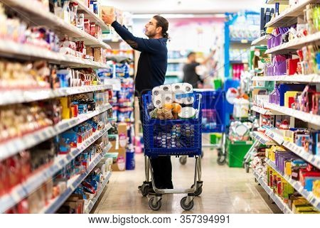 Full Shopping Cart, Customer Is Stocking Vital Needs Because Of Global Chaos. Shopping With Blur Sup