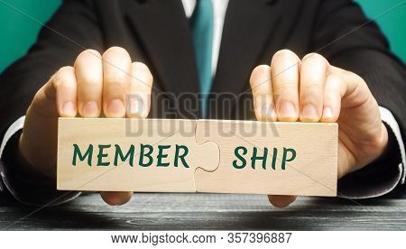 Businessman Collects Wooden Puzzles With The Words Membership. Belonging Of People To The Organizati