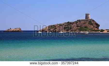 Ancient Historical Fortress In A Bay With Ships In The Front, Sardinia, Italy