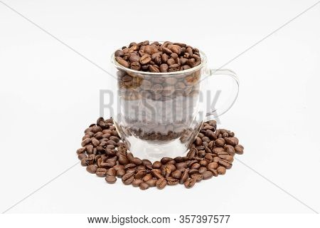 Glass Thermos Insulating Cup Transparent Overfilled With Roasted Coffee Beans On A White Underground