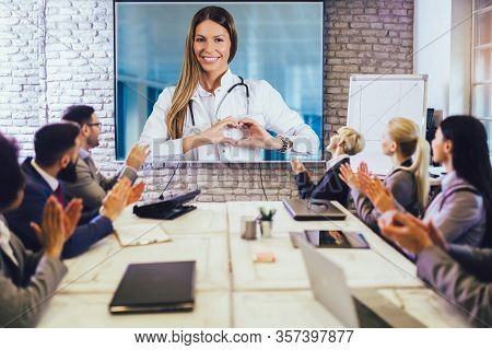 Team Of Business People Looking Doctor Speech At Projector Screen In Video Conference. Doctor Making