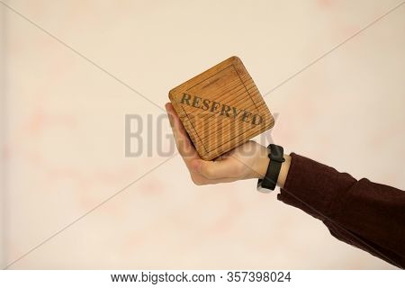 A Wooden Plaque Has A Word Reserved . Male Hand Holds A Wooden Plate With The Inscription Reserved I