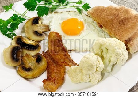 Breakfast. Bacon And Eggs With Vegetables On A White Plate. White Bread, Cauliflower, Parsley, Mushr