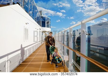 Happy Cute Little Toddler Girl On Arms Of Dad On Cruise Ship. Adorable Baby Child And Father, Middle