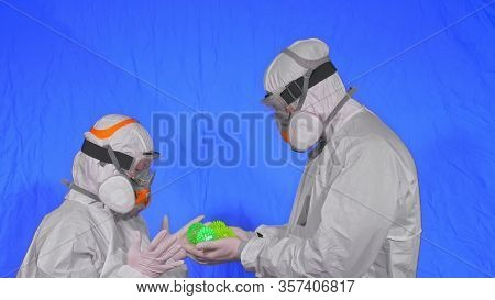 Doctor In Respirator Show A Virus Model. Slow Motion. Woman Wearing Protect Medical Aerosol Spray Pa