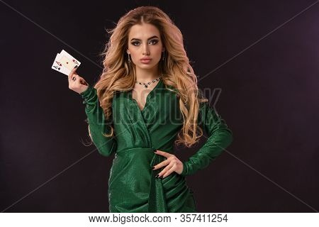 Blonde Girl With Make-up, In Green Stylish Dress And Jewelry. Put Hand On Hip, Showing Two Aces, Pos