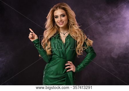 Blonde Girl In Green Stylish Dress And Jewelry. Smiling, Pointing At Something By Forefinger, Posing