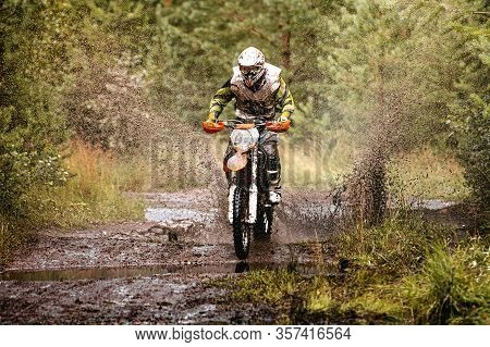 Motocross Enduro Race Athlete Riding On Muddy And Wet Trail In Forest