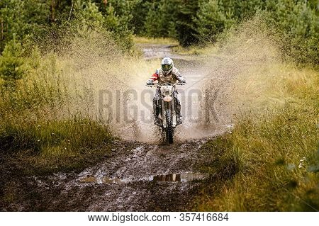 Dirty Motocross Racer Riding On Mud And Water In Enduro Race