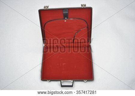 An Open Briefcase Is Lying On The Snow. On A White Background Is An Open Brown Briefcase. Top View O