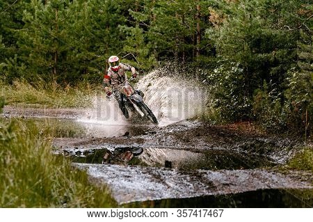 Motocross Rider Riding In Puddle With Splashes, Forest Enduro Race
