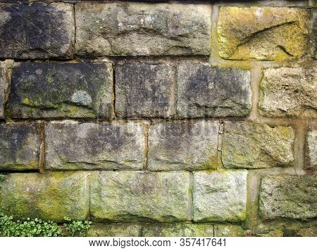 An Old Grey Damp Stone Wall Made Of Large Regular Blocks Covered In Patches Of Moss