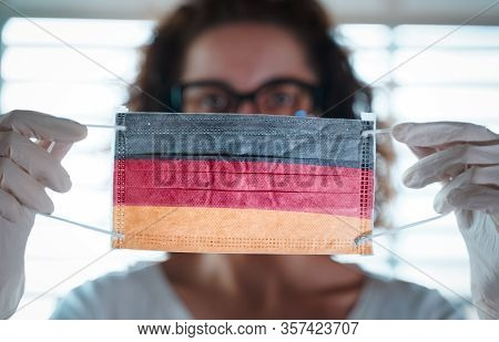 Pandemic Coronavirus. Close Up Of Young Woman With Surgical Mask With The Flag Of Germany On It