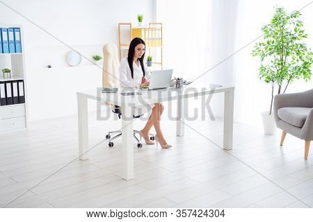 Full Length Photo Of Beautiful Doc Lady Use Modern Technology Notebook On Table Attentive Read Patie