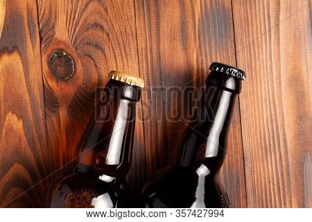 Two Bottles Of Beer Lie On An Open Table With Empty Space.
