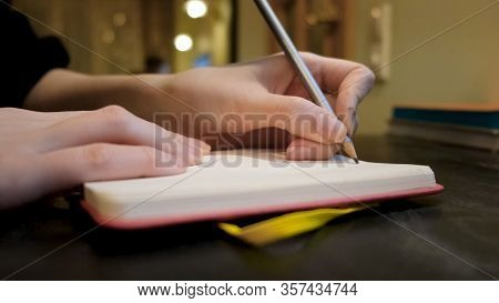 Close-up Of Woman Writing Something In Notebook In Cafe. Concept. Woman Writes Down Something Person