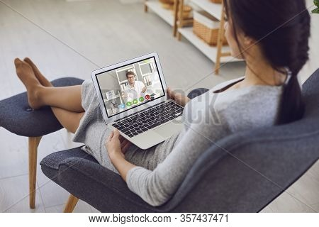 Online Medical Consultation..a Sick Young Woman Video Chat With A Male Doctor Sitting At Home.