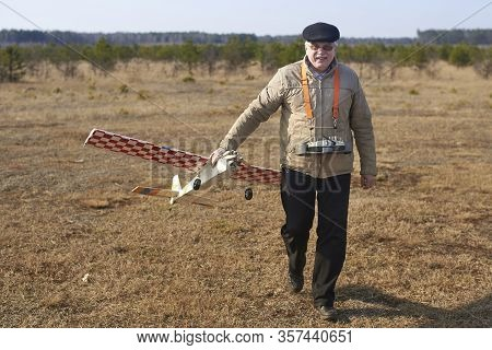 Elderly Man Holds Rc Airplane With A Broken Propeller After The Crash.