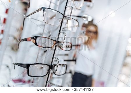 Optical Shop. Optician Suggest Glasses. Woman Standing With Many Eyeglasses In Background.