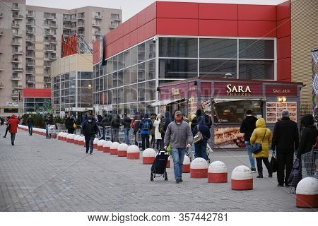 Bucharest, Romania - March 24, 2020: Shoppers Stand In A Queue Outside A Supermarket, After A Corona