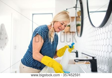 Senior Woman With Gloves Cleaning Bathroom Indoors At Home.