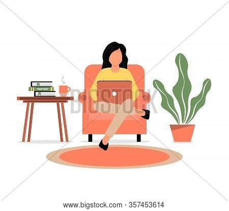 A Girl Sits In A Chair And Works On A Laptop. Home Office. Work At Home Or Freelance. A Young Woman