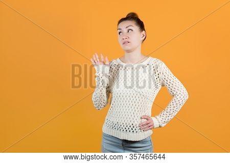 The Girl Skeptically Dismisses Someone. Isolated On Orange Yellow Background.