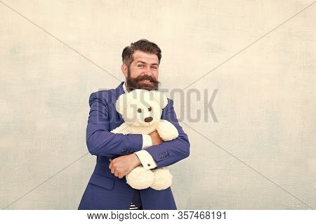 His Favorite Toy Friend. Happy Businessman Hug Teddy Bear Blue Background. Bearded Man Smile With To