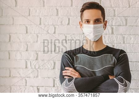 Portrait Confident Sports Man With Crossed Arms In Medical Face Mask. Personal Protection Against Co