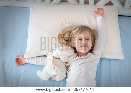 Cute Adorable Caucasian Blond Little Toddler Kid Girl Lying In Bed On White Pillow. Adorable Sweet H