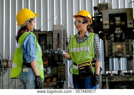 Factory Woman Technician Or Worker Give Wrench To Her Co-worker In Front Of Machine With Day Light.