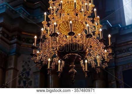 Big Bronze Chandelier With Electric Candles In Cathedral Christian Church. Selective Focus