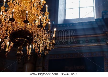Big Bronze Chandelier With Electric Candles In Cathedral Christian Church. Daylight From The Window