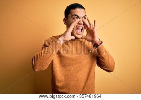 Young brazilian man wearing casual sweater standing over isolated yellow background Shouting angry out loud with hands over mouth