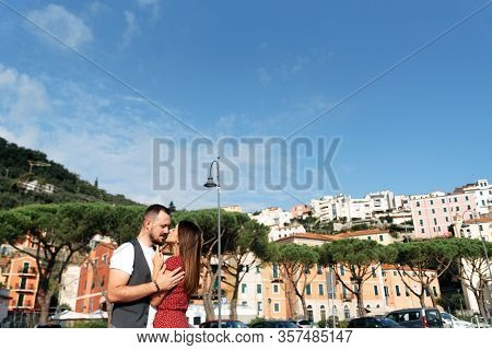 Love Story In Italy. A Couple In Love Are Standing In An Embrace, A Beautiful Girl In A Dress And An