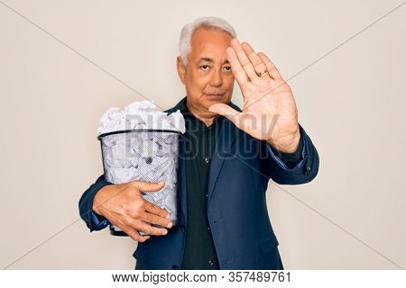 Middle age senior grey-haired business man holding paper bin full of rubbish documents with open hand doing stop sign with serious and confident expression, defense gesture