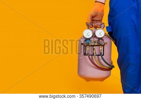 A Male Air Conditioner Repairman Is Holding A Freon Cylinder And A Pressure Measurement Sensor In Hi