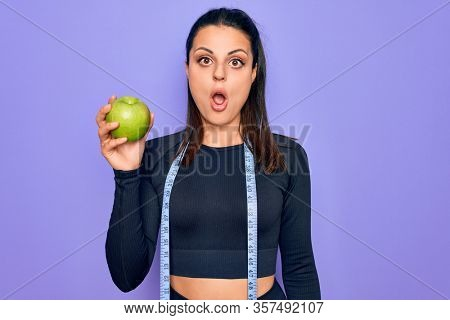 Beautiful brunette sporty woman using tape measure eating apple fruit over purple background scared and amazed with open mouth for surprise, disbelief face