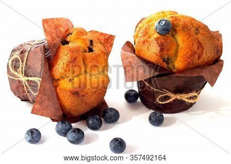 Two Appetizing Fresh Muffin Muffins Lie On An Isolated White Surface.