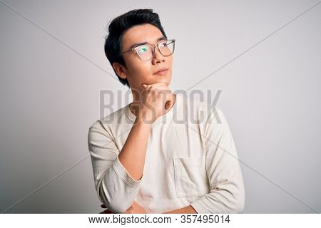Young handsome chinese man wearing casual t-shirt and glasses over white background with hand on chin thinking about question, pensive expression. Smiling with thoughtful face. Doubt concept.