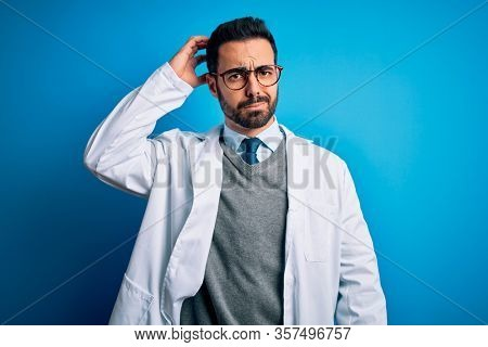 Young handsome doctor man with beard wearing coat and glasses over blue background confuse and wonder about question. Uncertain with doubt, thinking with hand on head. Pensive concept.