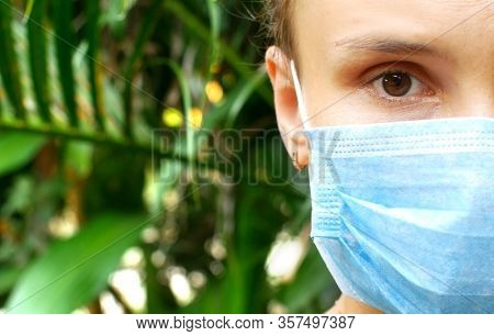 The coronavirus epidemic, a woman in a mask looks into the frame.