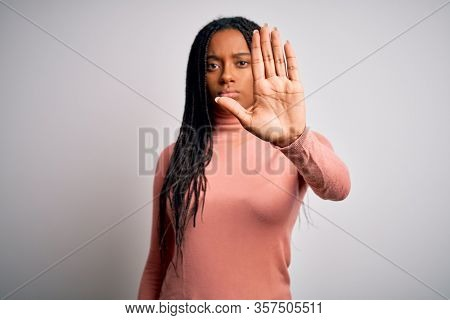 Young african american woman standing casual and cool over white isolated background doing stop sing with palm of the hand. Warning expression with negative and serious gesture on the face.