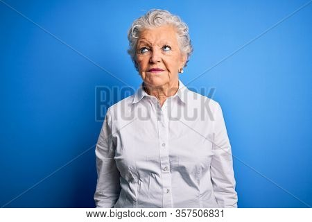 Senior beautiful woman wearing elegant shirt standing over isolated blue background smiling looking to the side and staring away thinking.